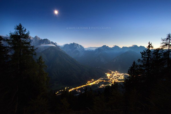 The city lights down in the Upper Sava valley illuminate streets in Kranjska Gora area. The moon is high up over the Julian Alps mountains. The walls of the highest peaks are still illuminated by the weak western skylight and moonlight.