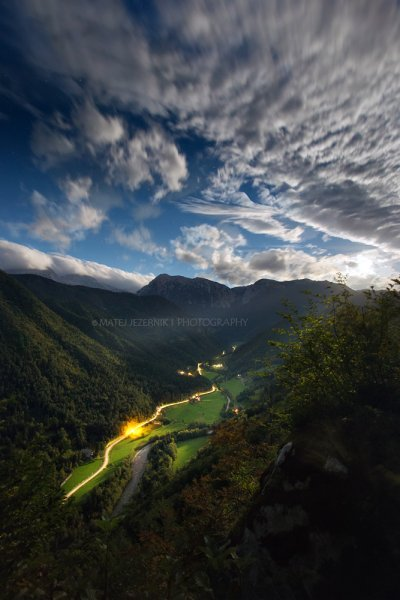 Full moon has just risen over the mountains in Slovenia. Moon rays are shining on the valley flor down there. Car trails folow the shape of the valley, disappearing in the distance as the valley turns toward north. The tranquility spreads over the landscape...