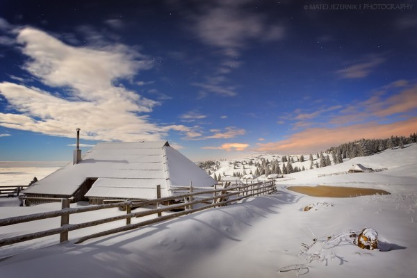 """First abundant snowfall of the winter season 2015-16 has come to Velika planina. The moonlight spreads over the vast pastures and wooden cottages. Through the openings in the clouds bright stars shine in this early evening. There is this peace up there, that you can only """"hear"""" when the snow covers the landscape..."""