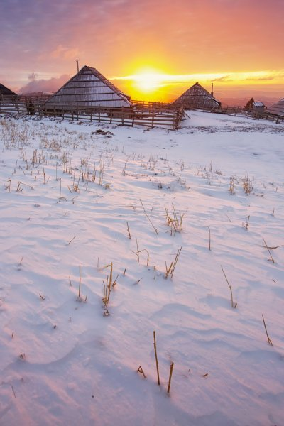 Warm colour of the morning sun is shining betwen two cottages in Velika planina area.