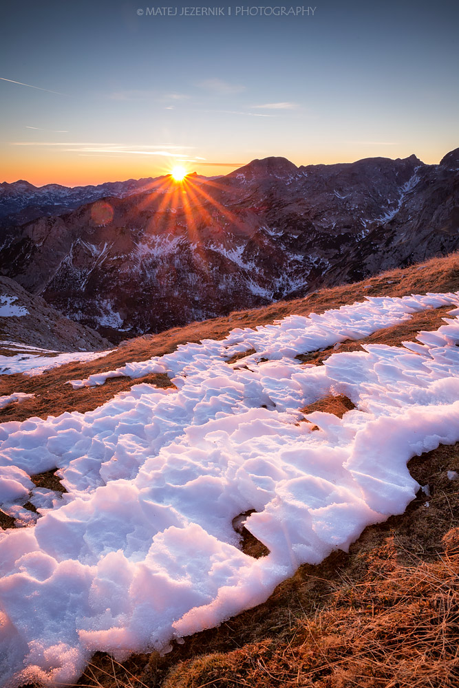 Sun is setting behind the Mount Krn on december evening in the Julian Alps.