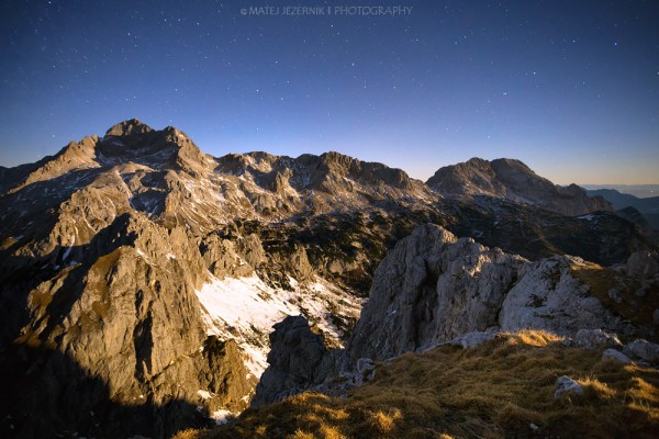Mount Triglav illuminated by moonlight as seen on late december evening from mount Tosc.